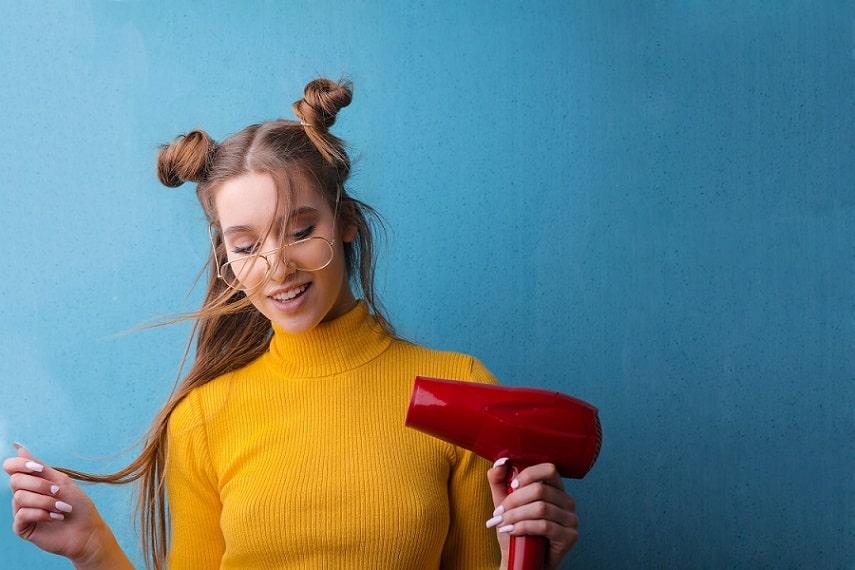 בחורה בלונדינית עם משקפיים עושה פוזות למצלמה על רקע כחול