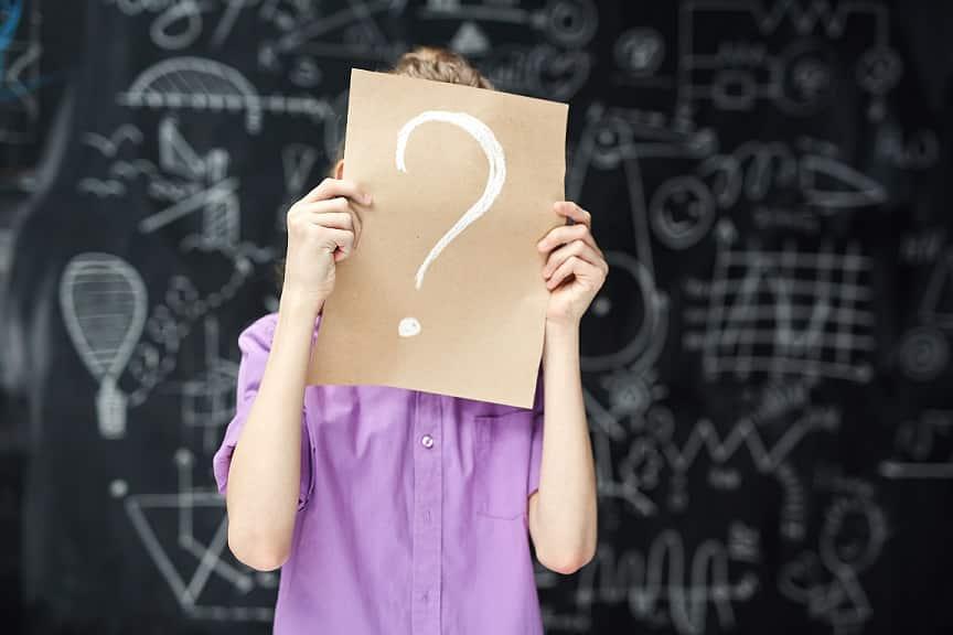 בחורה מחזיקה פיסת נייר מקרטון שיש עליה סימן שאלה