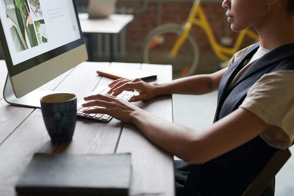 בחורה צעירה יושבת מול המחשב וכותבת מדריכי קנייה על נושאים שונים