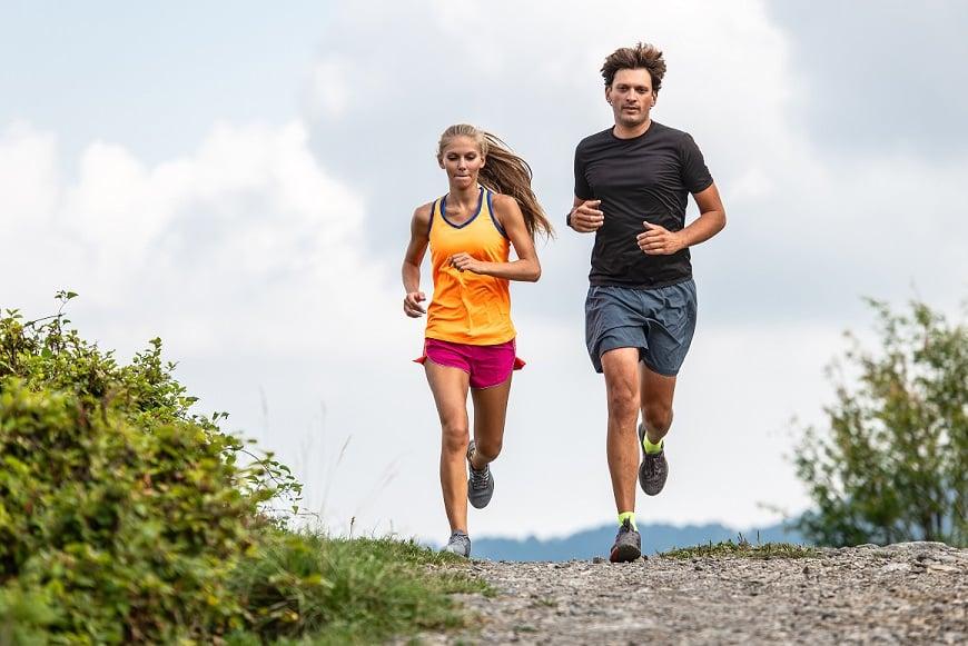 בחור ובחורה רצים על שביל אפר בהרים