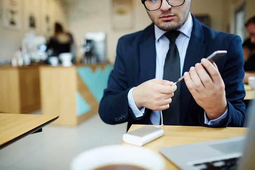 בחור צעיר בחליפה כחולה עם עניבה מטעין את הטלפון הסלולרי שלו
