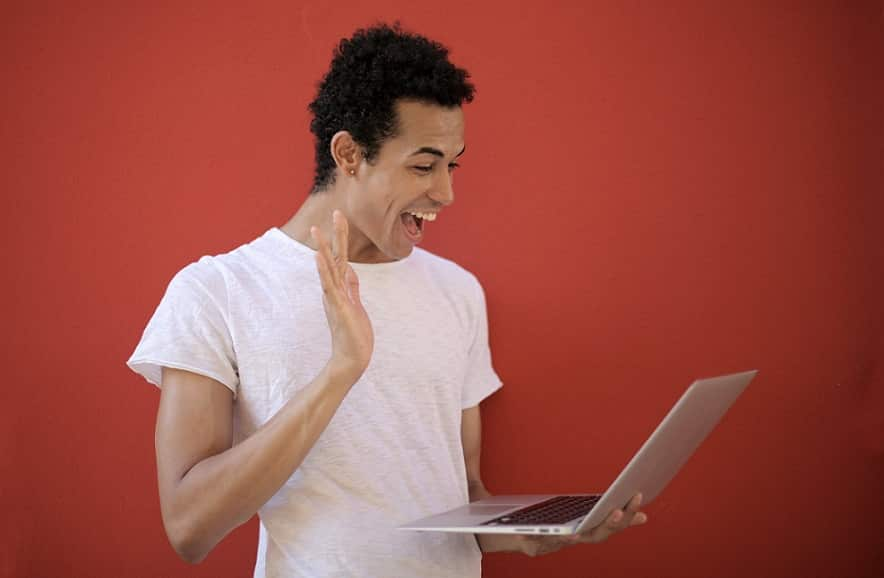 בחור צעיר ומתולתל מביט בהפתעה על מסך המחשב שלו ועומד על רקע בורדו