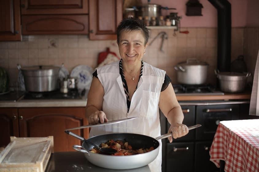 בשלנית מבוגרת מראה את הבישולים שלה במטבח הביתי ומחייכת