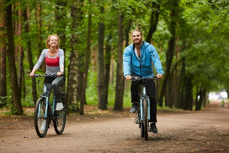 זוג צעיר רוכבים על אופניים ביער על רקע של עצים