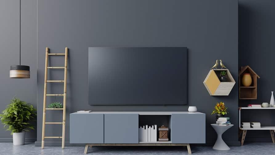 טלוויזיה חכמה עומדת בסלון ליד סולם וחפצים שונים