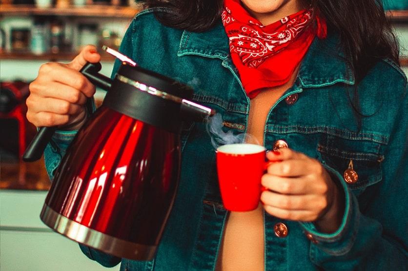 ידיים של בחורה מוזגות נוזל רותח לתוך כוס בצבע אדום