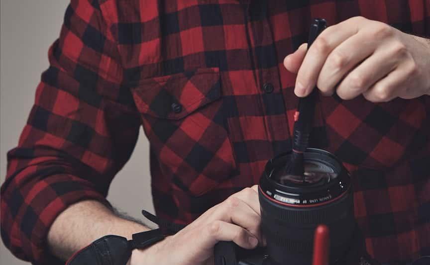 ידיים של גבר מנקות עדשה של מצלמה