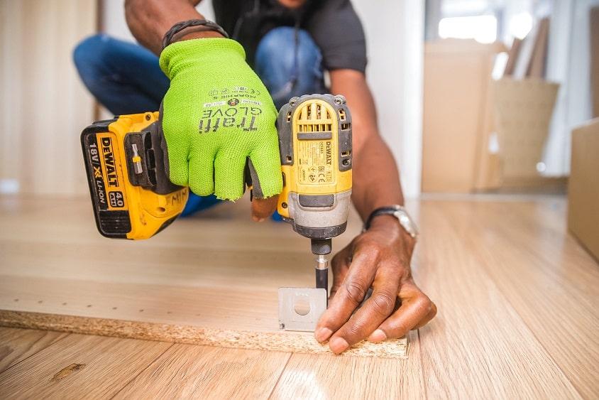 ידיים של גבר קודחות בעץ בזמן בנייה של סאונה בבית