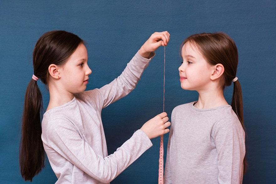 ילדה מודדת את חברה שלה עם סרט מדידה