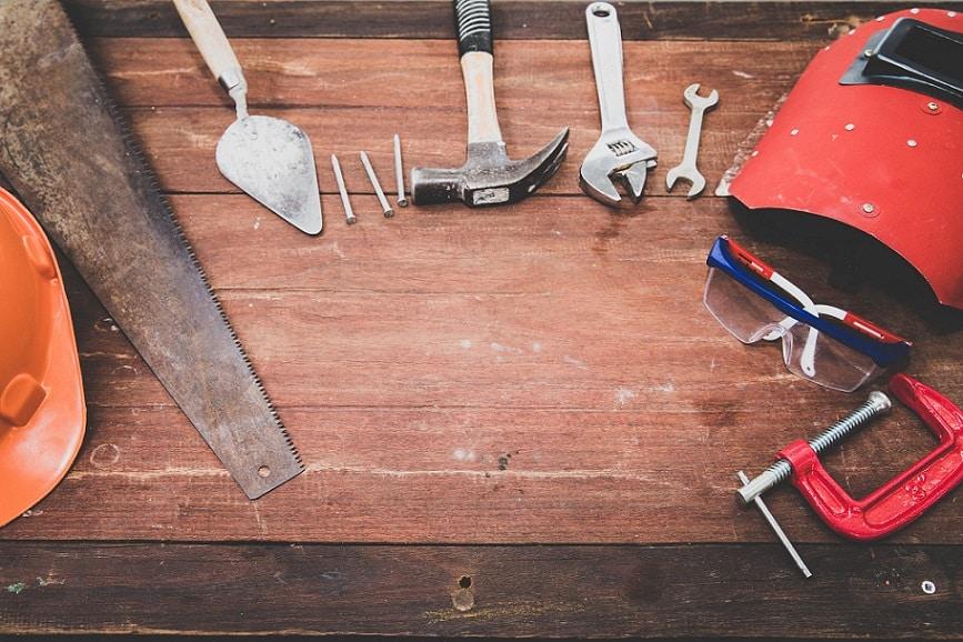 כלים שונים של בנייה והנדסה מונחים אחד ליד השני על שולחן