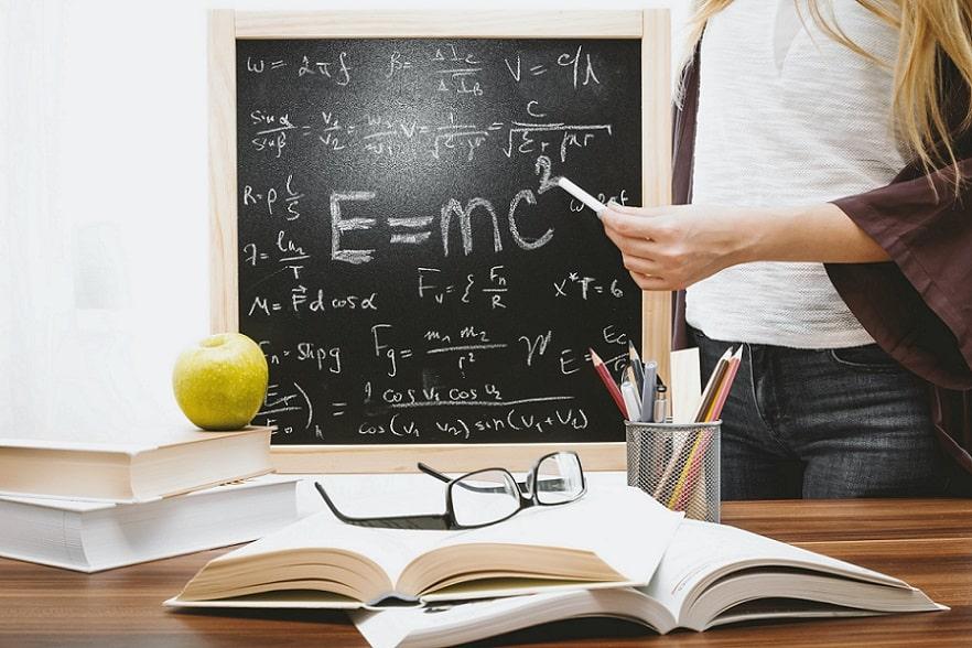 לוח גיר עם נוסחאות שונות עומד על שולחן ליד כלי כתיבה ספרים ותפוח