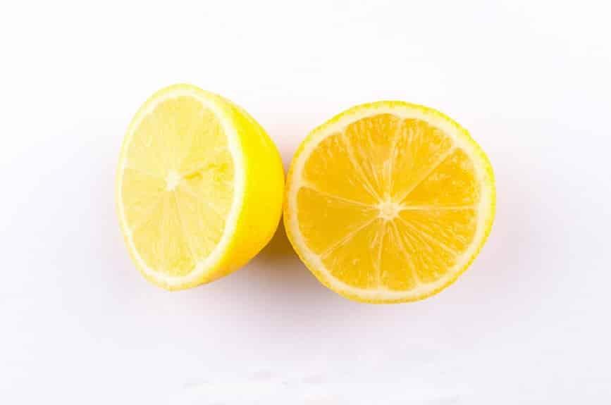 לימון טרי בצבע צהוב חזק פרוס ל-2 חלקים ששוכבים אחד ליד השני
