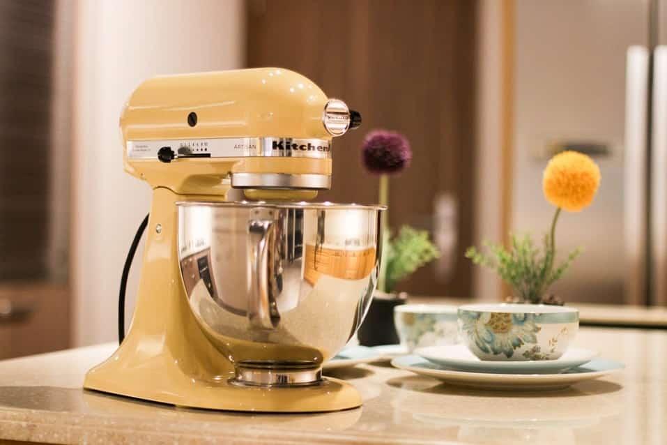 מכשיר חשמלי לערבוב מזון עומד על השולחן ליד כוס תה וכמה צלוחיות קטנות