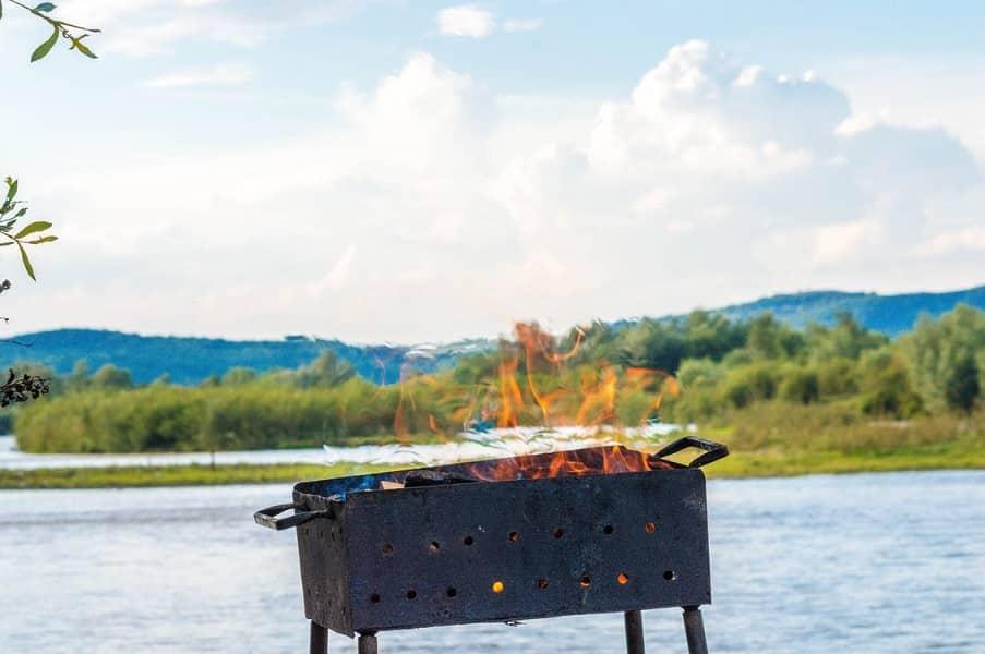 מנגל פחמים גדול וישן עם אש בוערת עומד בחוץ על רקע של אגם