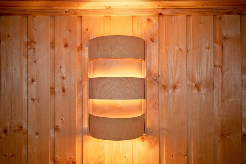 מנורת סאונה מעץ מחוברת לקיר של הסאונה