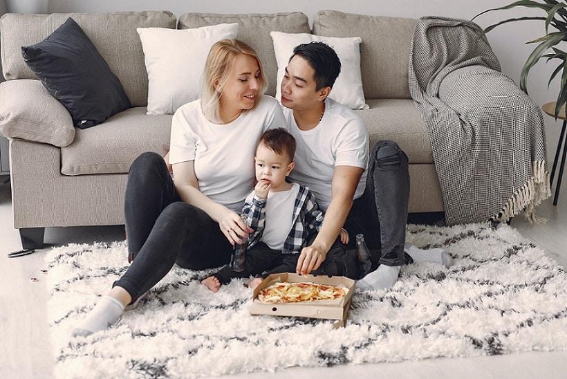 משפחה של אבא אמא וילד קטן יושבים בסלון על הרצפה ואוכלים פיצה