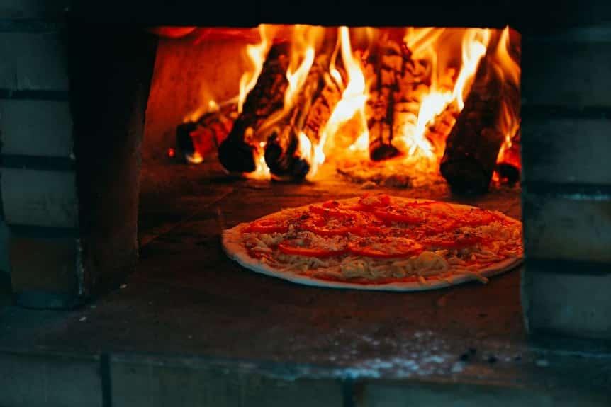 פיצה נאפת בתוך תנור עם פחמים לוהטות שבוערות באש