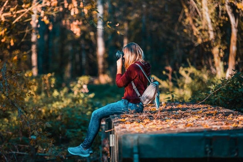 צלמת צעירה יושבת בטבע ומצלמת את העצים ואת היער