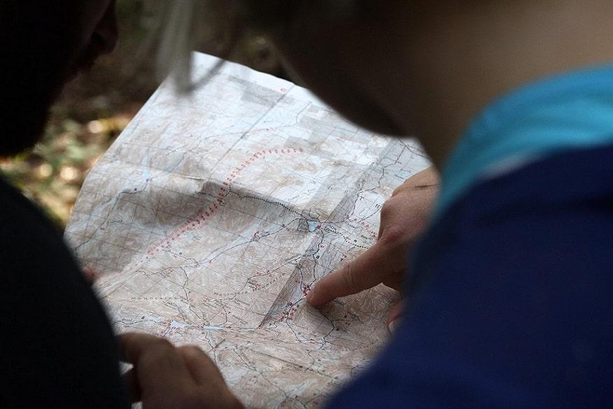 שני אנשים מסתכלים על מפה לבחירת מיקום ומצביעים עליה עם האצבע