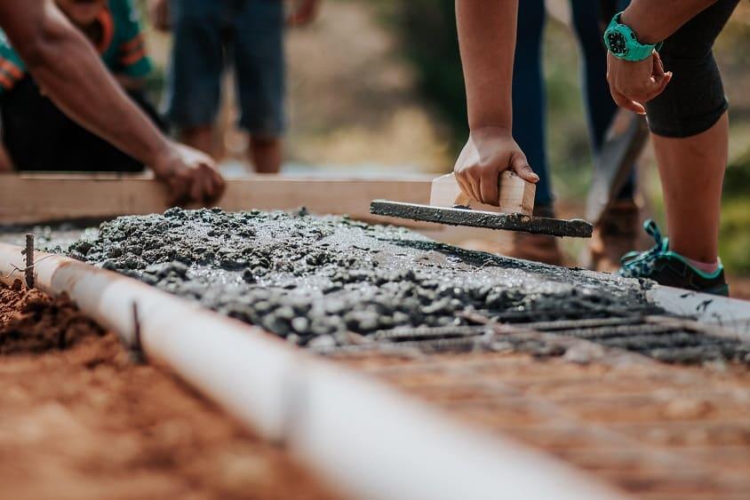 2 עובדים עם שפכטל ובטון בונים את היסודות של משהו על הקרקע