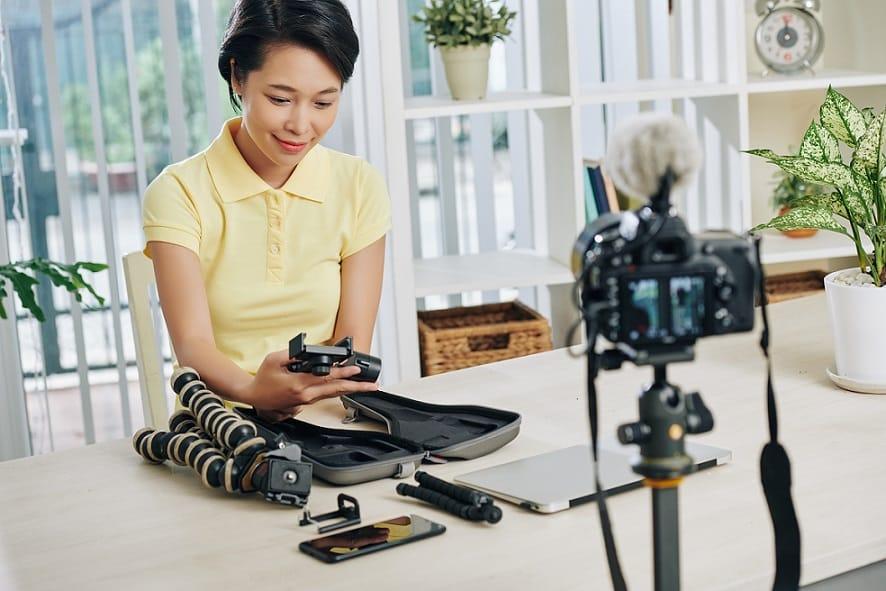 אישה אסייתית מצלמת וידאו סקירה עם שאלות ותשובות בנושא צילום