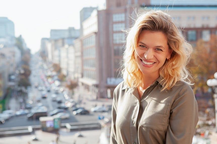 אישה בלונדינית מחייכת למצלמה על רקע של עיר גדולה מאחוריה