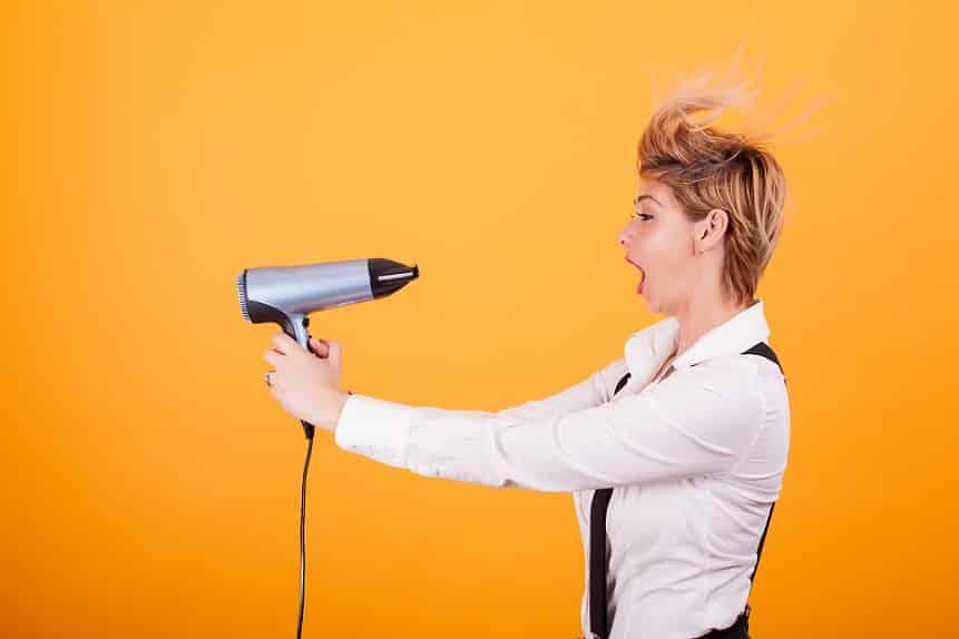 אישה עם שיער קצר מפזרת על עצמה אוויר חם על רקע כתום