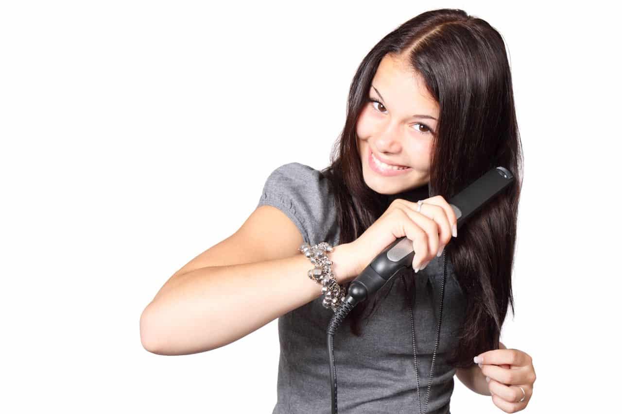 אישה צעירה עם שיער שחור משתמשת במחליק שיער ומסתכלת למצלמה