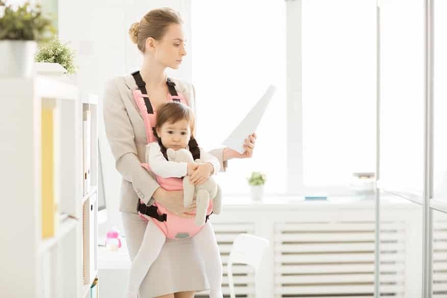אמא צעירה קוראת מדריך מדף נייר בזמן שהיא מחזיקה את הבת שלה