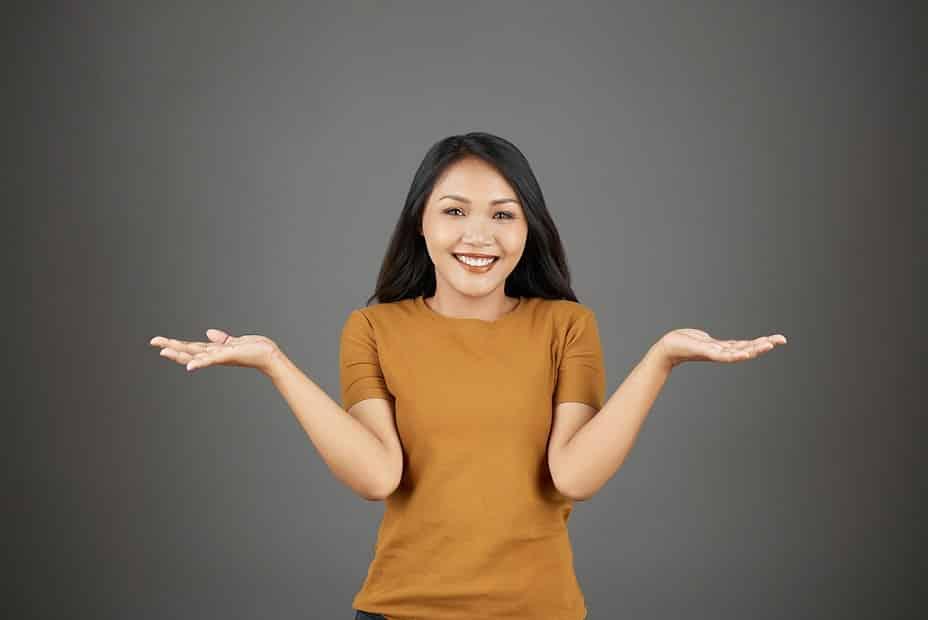 בחורה אסייתית צעירה עם שיער שחור עושה תנועה עם הידיים של שאלה