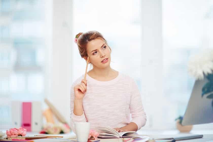 בחורה בלונדינית צעירה נושכת את העיפרון שלה וחושבת על משהו