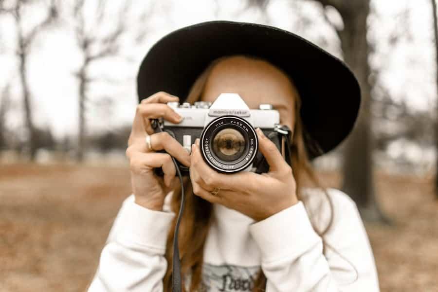 בחורה עם כובע עושה פוקוס על המסך ומצלמת