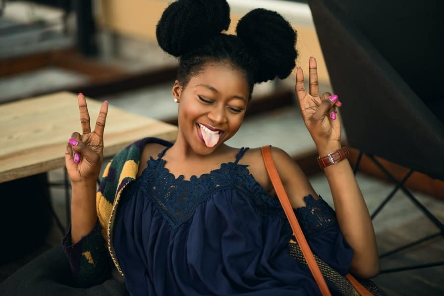 בחורה צעירה עם 2 קוקיות מגניבות מוציאה לשון ועושה פרצופים