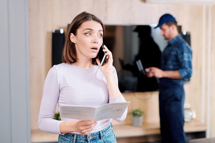 בחורה צעירה שואלת שאלות לגבי העלון שהיא מחזיקה עם טכנאי ברקע