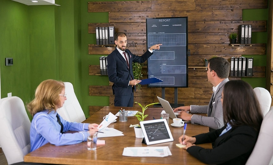 בחור בחליפה מסביר לאנשים על מדריך מיוחד בפגישה שבועית