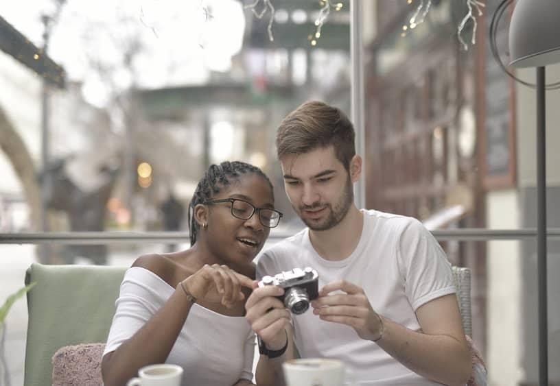 בחור ובחורה עם משקפיים בוחנים מקרוב מצלמה שהם אוהבים