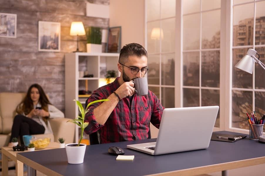 בחור עם חולצת משבצות שותה מכוס אפורה ומסתכל על דברים במחשב
