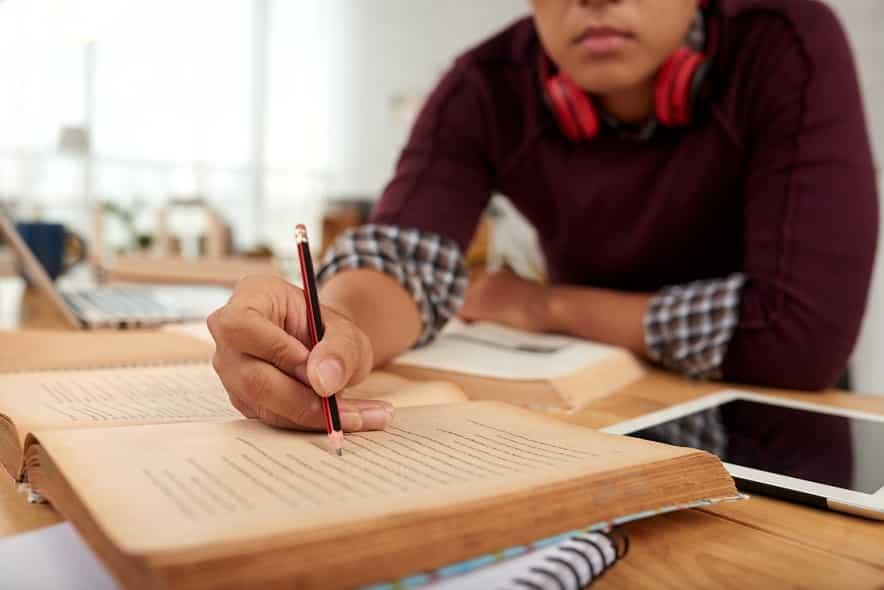 בחור צעיר בוחן מידע בספר גדול ומסמן אותו עם עיפרון שחור אדום