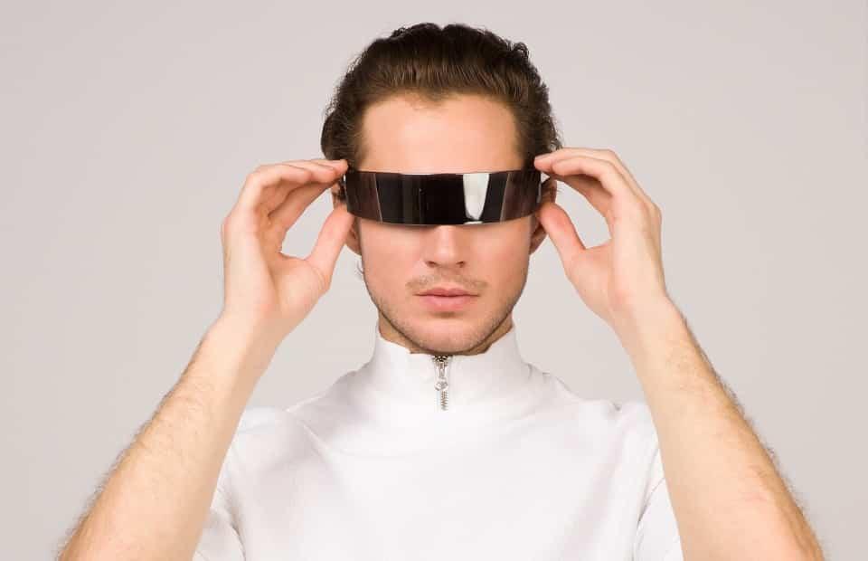 בחור צעיר לובש משקפיים עתידניות בצבע שחור ומסתכל על המסך