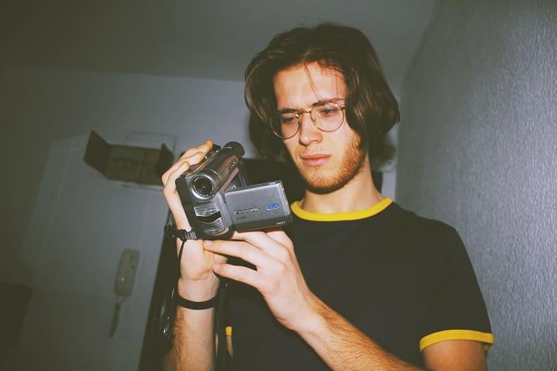 בחור צעיר מחזיק מצלמת וידאו ישנה ביד ומסתכל עליה