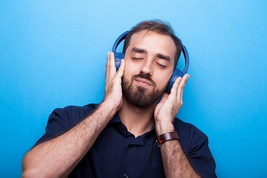 בחור צעיר עם זיפים מקשיב למוזיקה באוזניות כחולות ועוצם עיניים