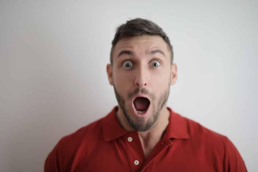 בחור צעיר עם חולצה אדומה פותח את הפה עם מבט מאוד מופתע