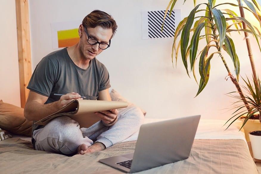 בחור צעיר עם משקפיים יושב על המיטה ורושם הערות שהוא קורא במדריך