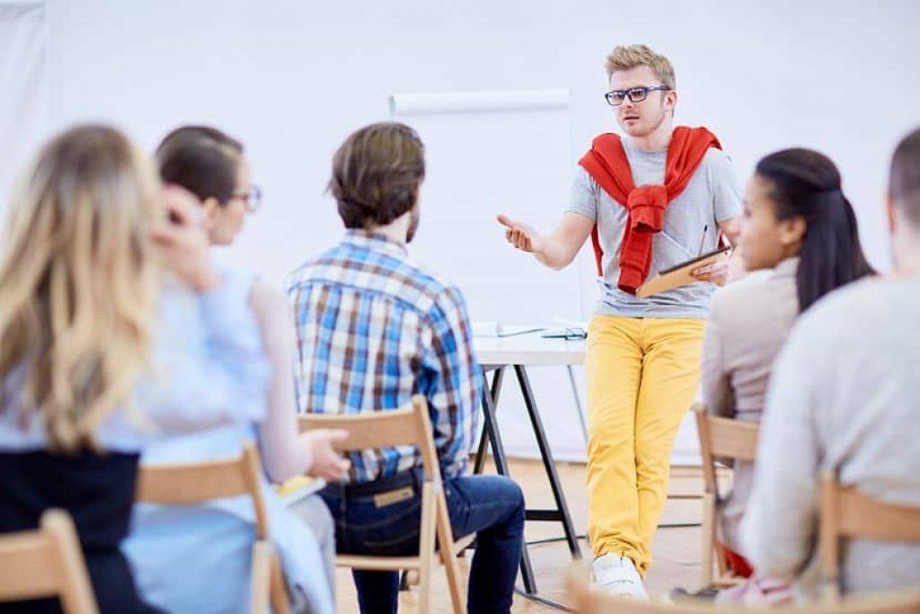בחור צעיר עם משקפיים כחולות מדריך חדר של אנשים על נושאים שונים