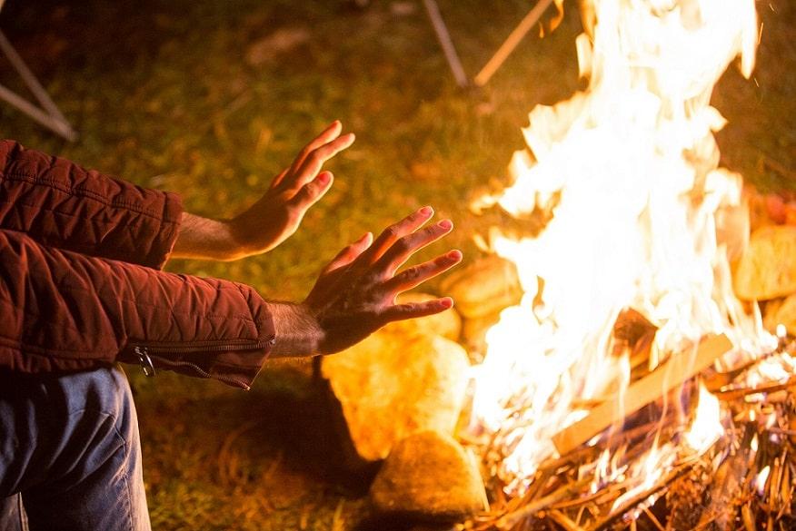 בן אדם מחמם את הידיים שלו על אש שבוערת מתוך מדורה בחוץ