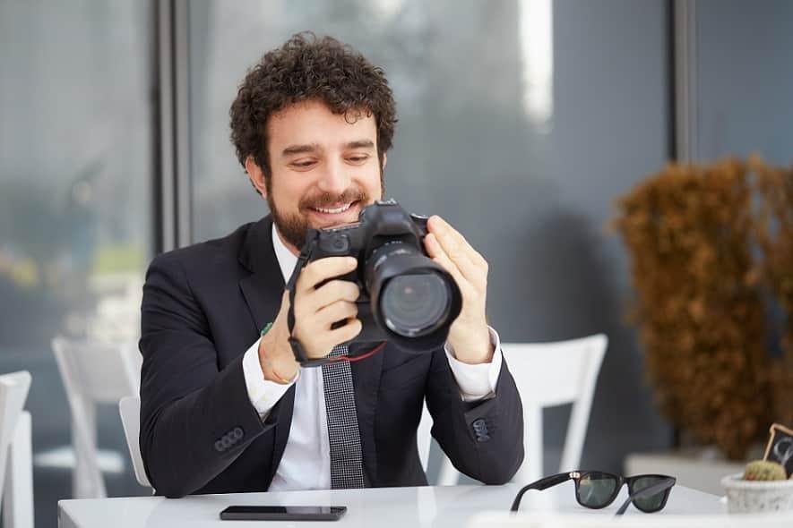 גבר בחליפה בודק את המצלמה שלו מכל הכיוונים