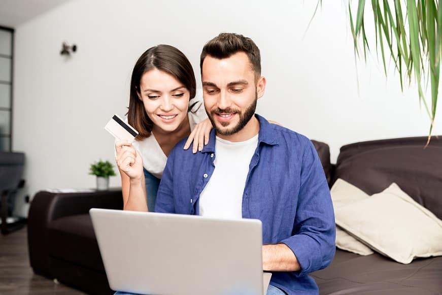 גבר ואישה מסתכלים על מסך של מחשב בזמן שהאישה מחזיקה כרטיס אשראי ביד