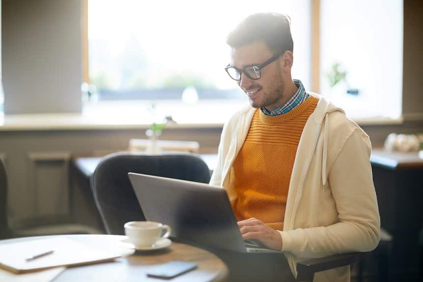גבר ממושקף יושב בבית קפה וקורא משהו באינטרנט שגורם לו לחייך