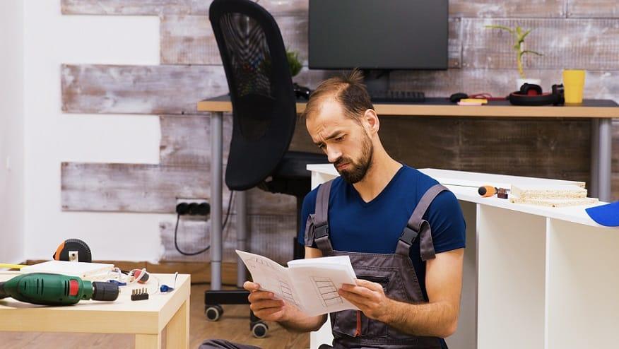 גבר צעיר ומקריח קורא הוראות התקנה של משהו וחושב