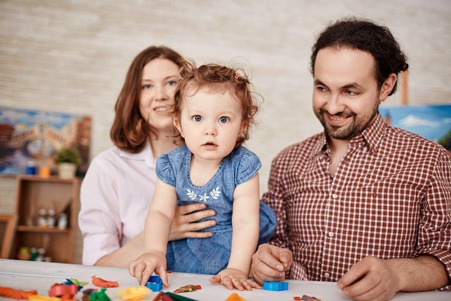 הורים מחזיקים את הבת הקטנה שלהם ביד ליד שולחן מלא במשחקים